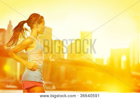 Running woman. Runner jogging in sunny bright light. Female fitness model training outside in New York City with skyline and Brooklyn Bridge in background.