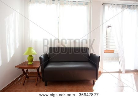 Black Sofa And A Lamp On The Bedside Table On A Background Of Curtains