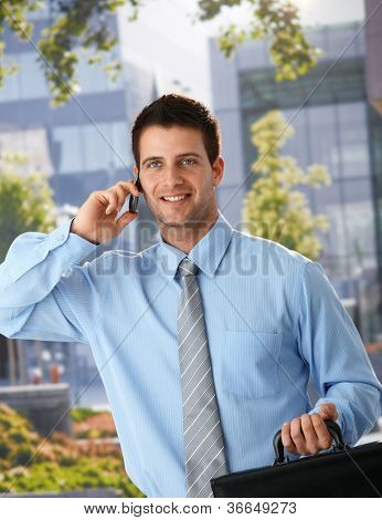 Happy businessman standing outside of office, speaking on mobile phone, holding briefcase.