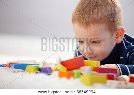 Liebenswert Ingwer-kurzhaarige kleine Junge spielt mit Würfel, lächelnd.