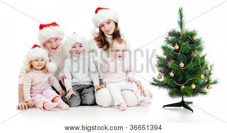 happy family in Santa's hats near christmas tree isolated on white