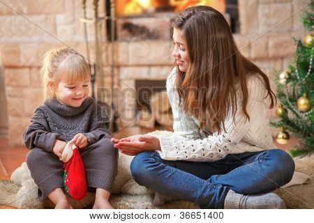 Two sisters sitting near christmas tree opening gifts
