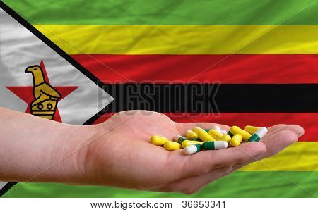 Holding Pills In Hand In Front Of Zimbabwe National Flag