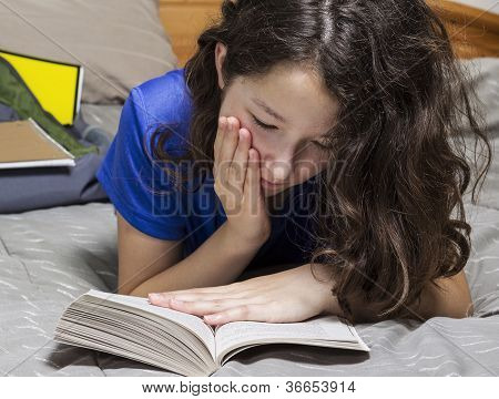 Young Girl Reading Book In Bedroom