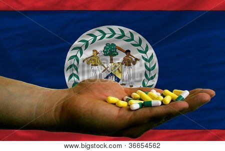Holding Pills In Hand In Front Of Belize National Flag
