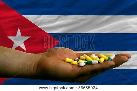 Holding Pills In Hand In Front Of Cuba National Flag