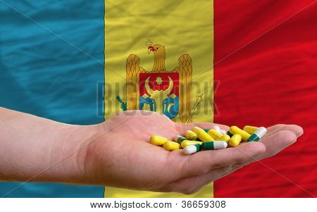 Holding Pills In Hand In Front Of Moldova National Flag