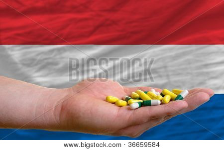 Holding Pills In Hand In Front Of Netherlands National Flag