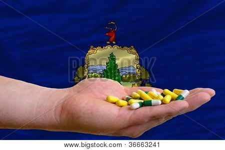 Holding Pills In Hand In Front Of Vermont Us State Flag