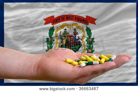 Holding Pills In Hand In Front Of West Virginia Us State Flag