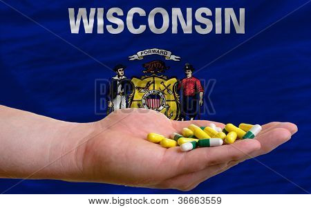 Holding Pills In Hand In Front Of Wisconsin Us State Flag
