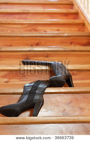 Wooden stairs with a pair of black womens boots