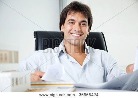 Portrait of happy young male architect with blueprint sitting in office chair
