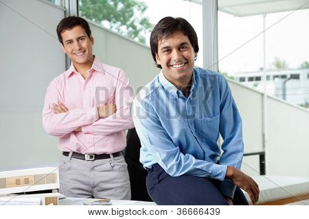 Portrait of young male architect smiling while colleague stands with arms crossed in background