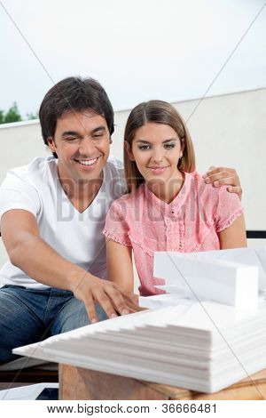 Happy young couple in casuals looking at an architectural model structure
