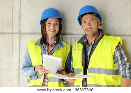 Construction team standing against building wall with blueprint