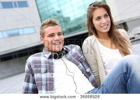 Young couple sitting outside the college building