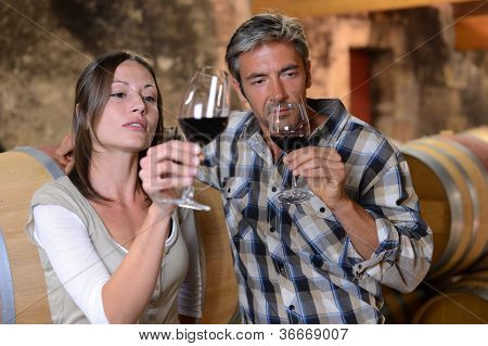 Couple of winemakers tasting red wine