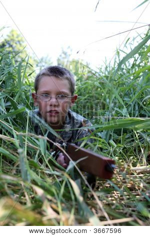 Child In Field With Toy Gun In The Grass