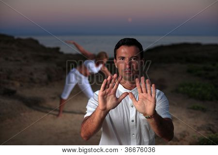 Handsome man on the beach meditating - Tai chi with woman practicing Yoga on background