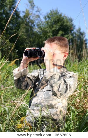 Young Boy Looking Through Binoculars In A Field