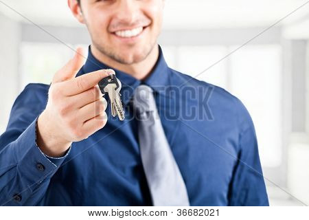 Smiling businessman giving keys to you