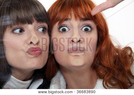 Friends making a silly face against a windowpane