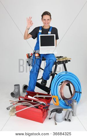 woman plumber showing laptop doing OK sign