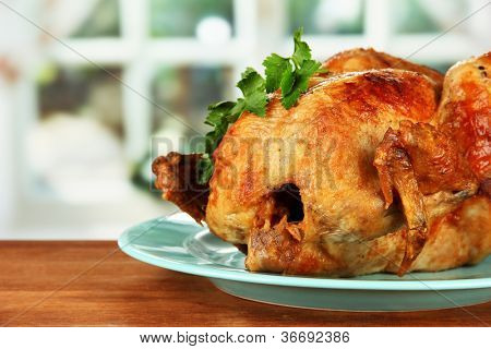 Roasted whole chicken on a blue plate on wooden background close-up