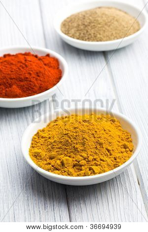 various colored spices in ceramic bowls