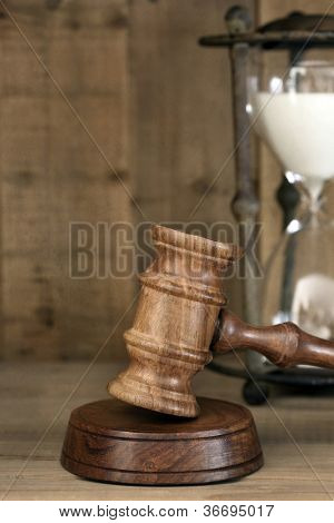 Old hourglass and wooden gavel, with grunge effects.  Time and justice concept.