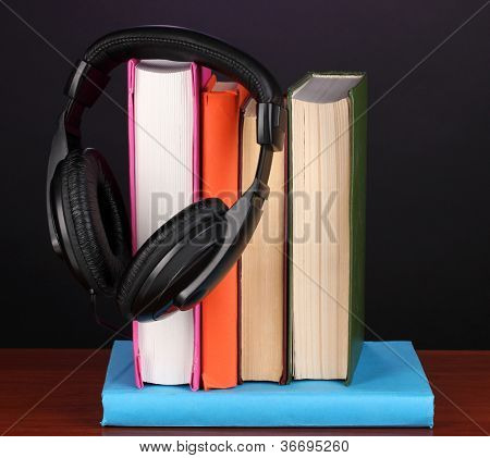 Headphones on books on wooden table on black background
