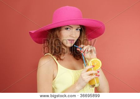 Smiling beautiful girl with beach hat and cocktail on pink background