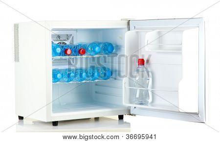 mini fridge full of bottled water isolated on white