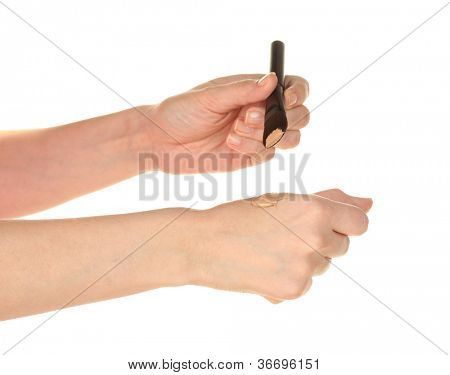 Woman applying concealer on hand on white background close-up