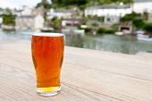 picture of differential  - A full pint of English real ale on a wooden table outside a riverside pub - JPG