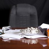 desk with ash tray piled with cigarettes and whiskey glass