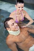 picture of neck brace  - Young man wearing neck brace in pool with beautiful woman - JPG