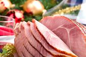 pic of christmas dinner  - Holiday table setting with delicious whole baked sliced ham vegetable salad and glasses of red wine - JPG