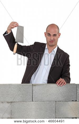 Office worker stood with trowel next to wall
