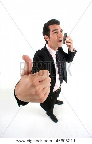 Businessman talking on his mobile phone and giving the thumb's up