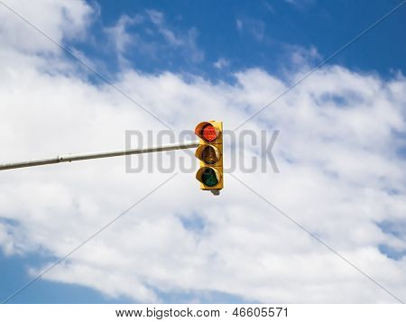 Red traffic light on cloud sky background. Photo.