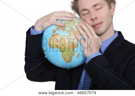 Businessman hugging a globe