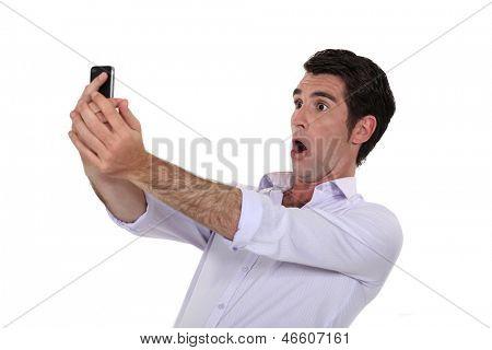 Homem surpreendido assistindo seu telefone móvel