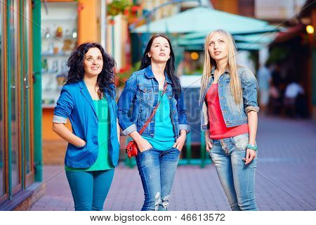Three Young Girls Stand Still In Daze, Looking Upward. Advertizing Impact