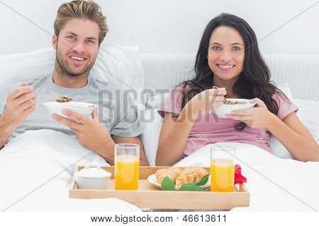 Couple eating cereal during a romantic breakfast in bed