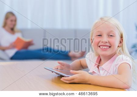 Little girl using tablet pc in the living room while her mother is reading a book