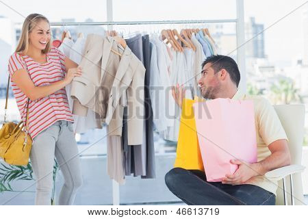 Depressed man looking at his shopaholic girlfriend in a clothing store