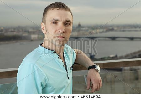 A Young Man In A Turquoise Shirt, Short Sleeve, Portrait Against The Background Of A European City.