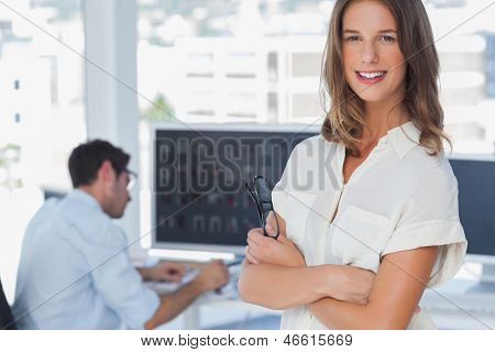Pretty photo editor standing with arms folded with colleague working behind
